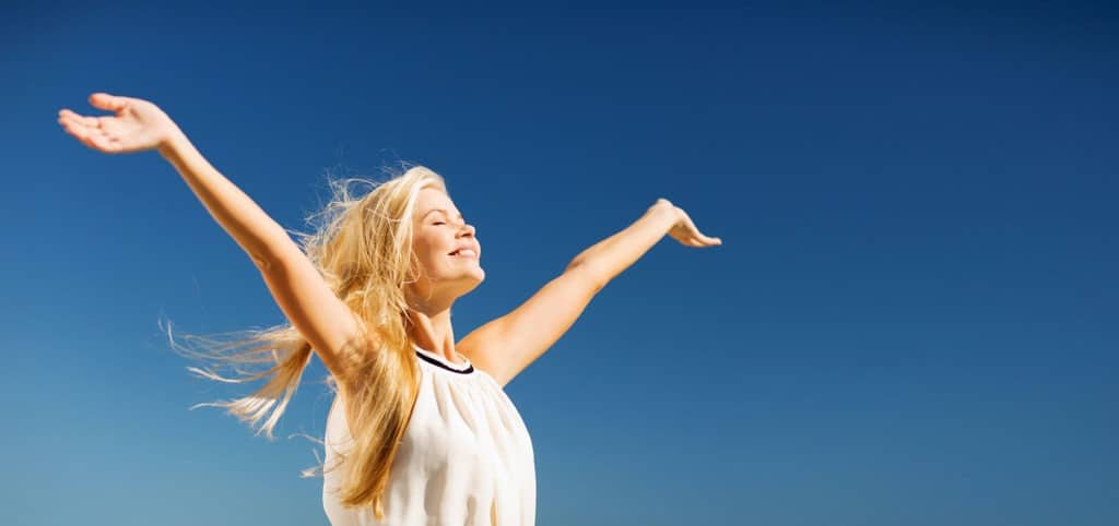 Blonde woman with arms open against blue sky